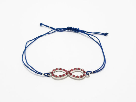 Bracelet with infinity symbol decorated with small red crystal beads